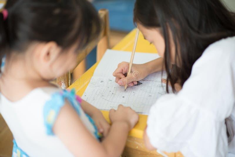Pequeña escritura asiática de la muchacha en la escuela del cuaderno fotos de archivo libres de regalías
