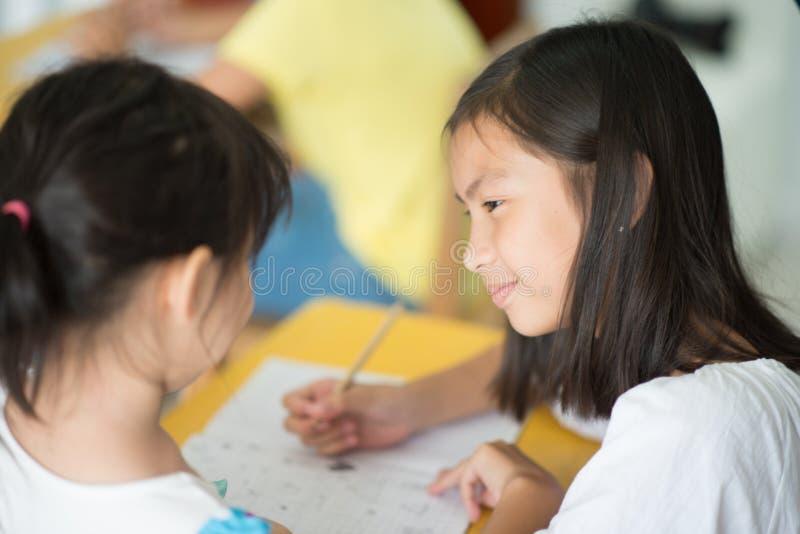 Pequeña escritura asiática de la muchacha en la escuela del cuaderno fotos de archivo