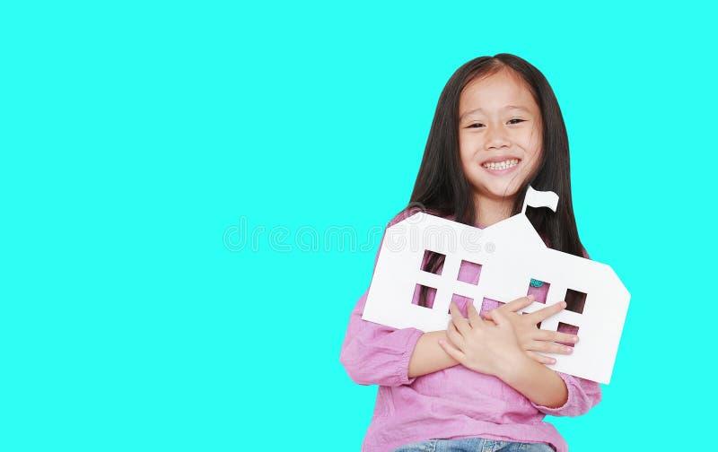 Pequeña escuela asiática feliz del papel de la maqueta del abarcamiento de la muchacha del niño aislada sobre fondo ciánico con e fotos de archivo libres de regalías