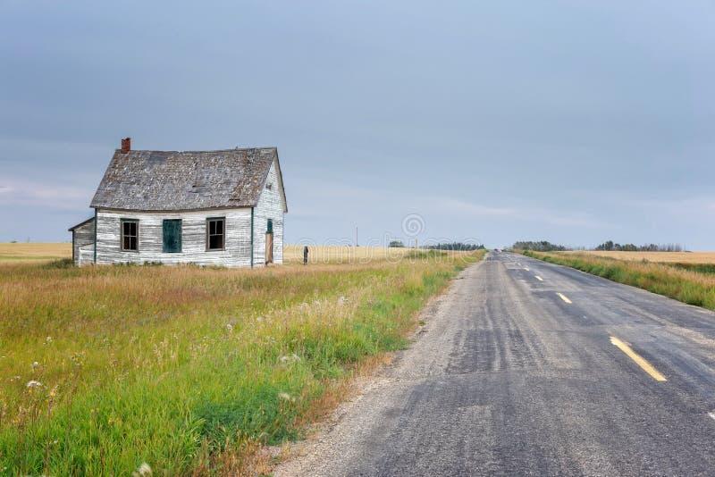 Pequeña escuela de país abandonada vieja que se sienta al lado de una carretera estrecha foto de archivo