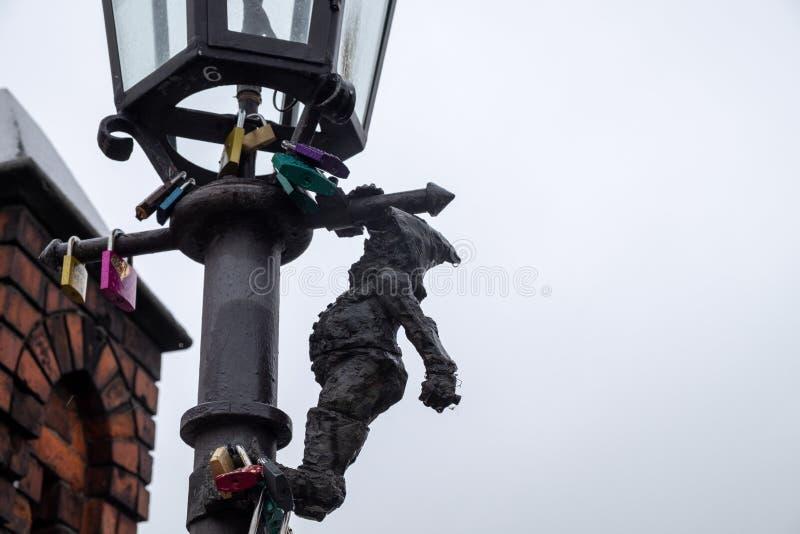 Pequeña escultura del farolero de bronce del gnomo en la linterna de la calle en Wroclaw fotos de archivo