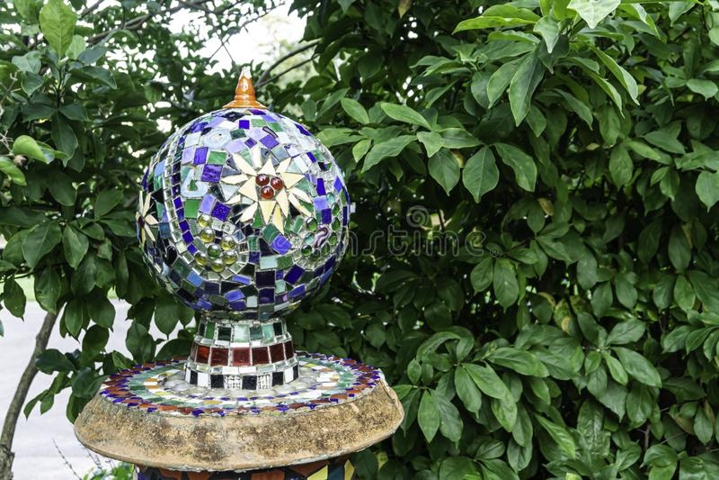 Pequeña esfera del orbe de las tejas del mosaico en jardín con las hojas verdes en contexto del fondo fotos de archivo libres de regalías