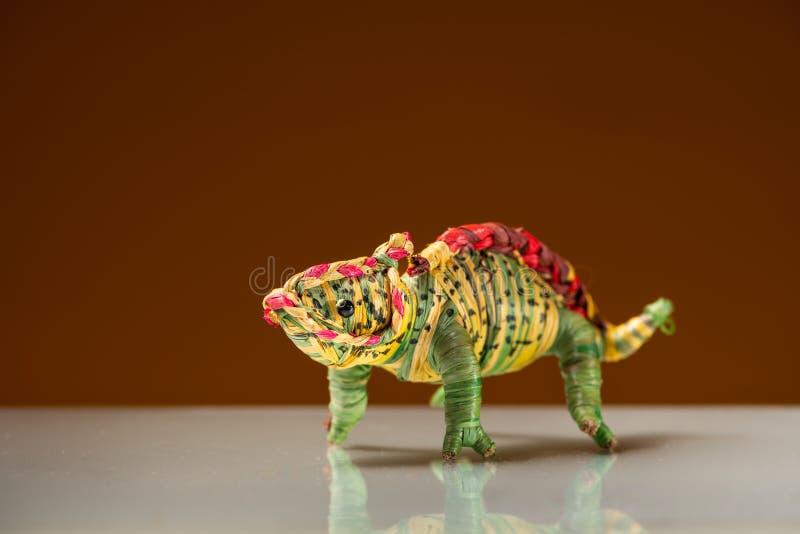 Pequeña estatuilla colorida de un dinosaurio, fondo marrón imágenes de archivo libres de regalías