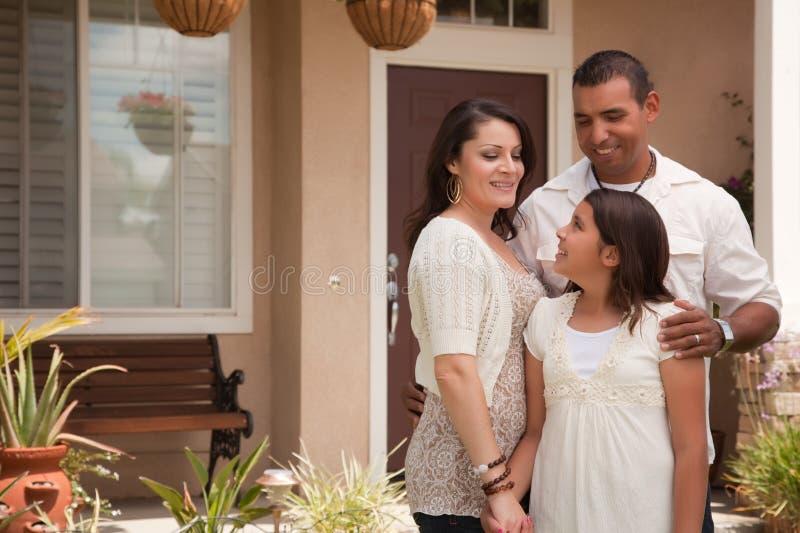 Pequeña familia hispánica delante de su hogar