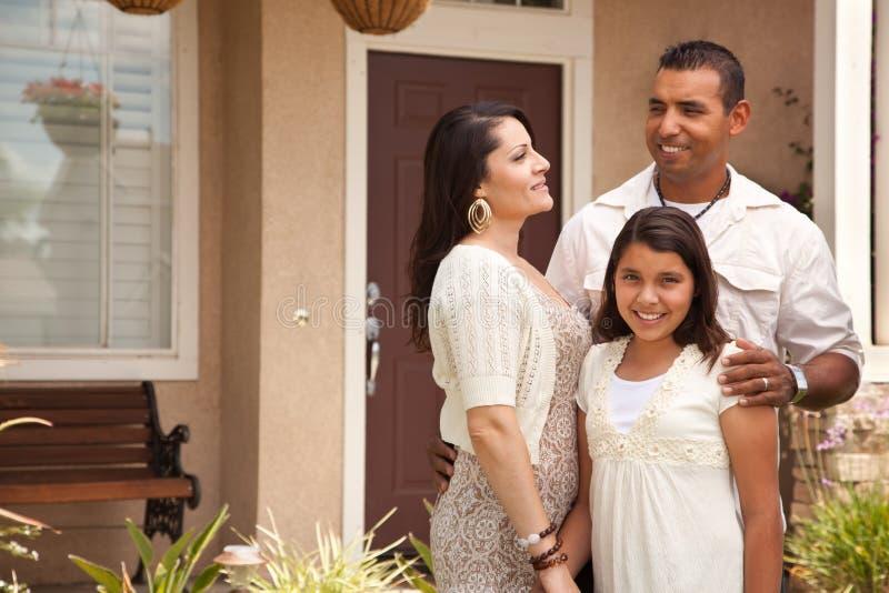 Pequeña familia hispánica feliz delante de su hogar fotografía de archivo