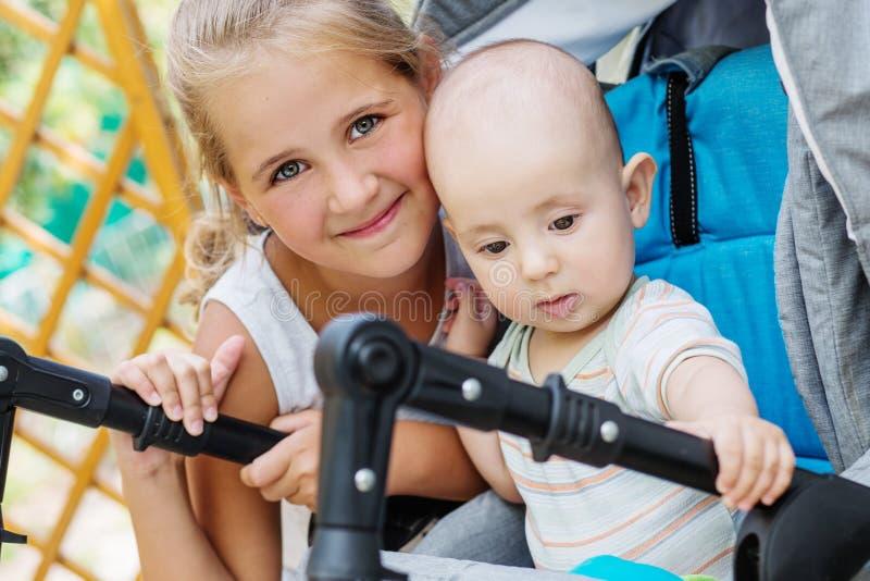 Pequeña hermana feliz que abraza al hermano del bebé imagenes de archivo