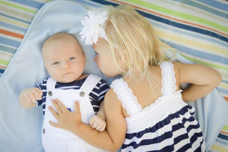 Pequeña hermana Laying Next a su bebé Brother en la manta imagenes de archivo