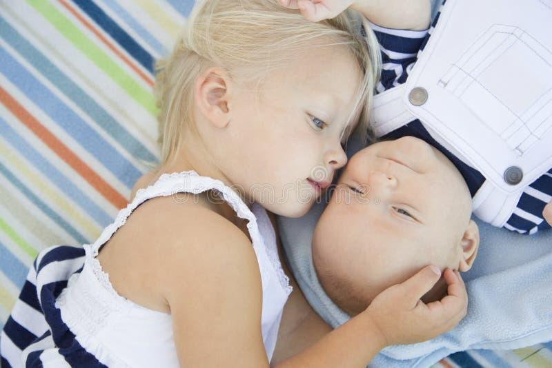 Pequeña hermana Laying Next a su bebé Brother en la manta foto de archivo libre de regalías