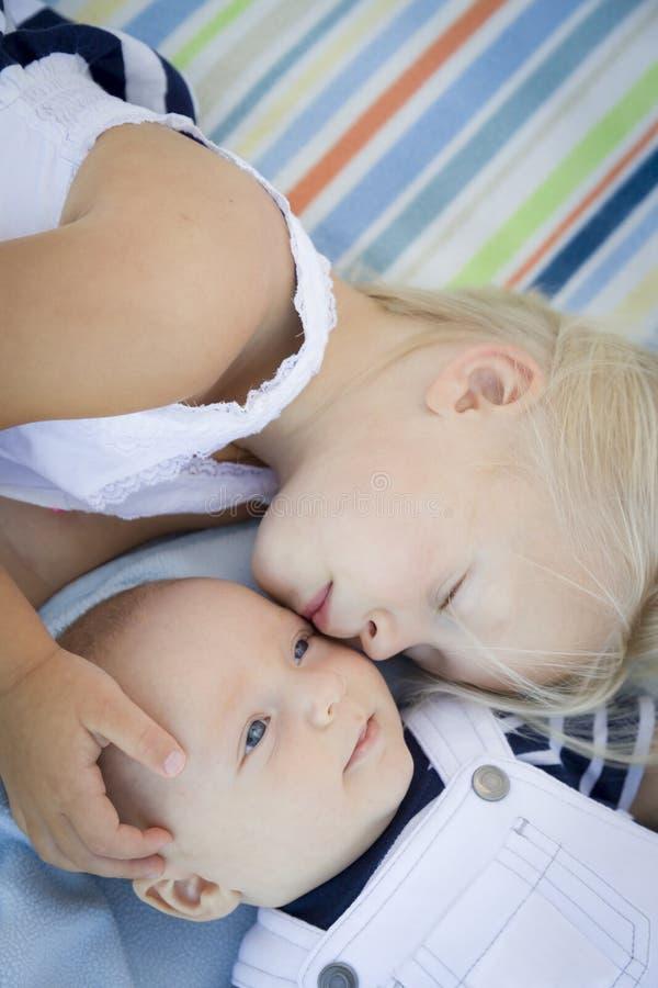 Pequeña hermana Laying Next a su bebé Brother en la manta foto de archivo