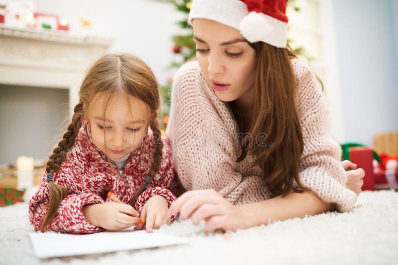 Pequeña hija de ayuda con la decoración de la Navidad imágenes de archivo libres de regalías