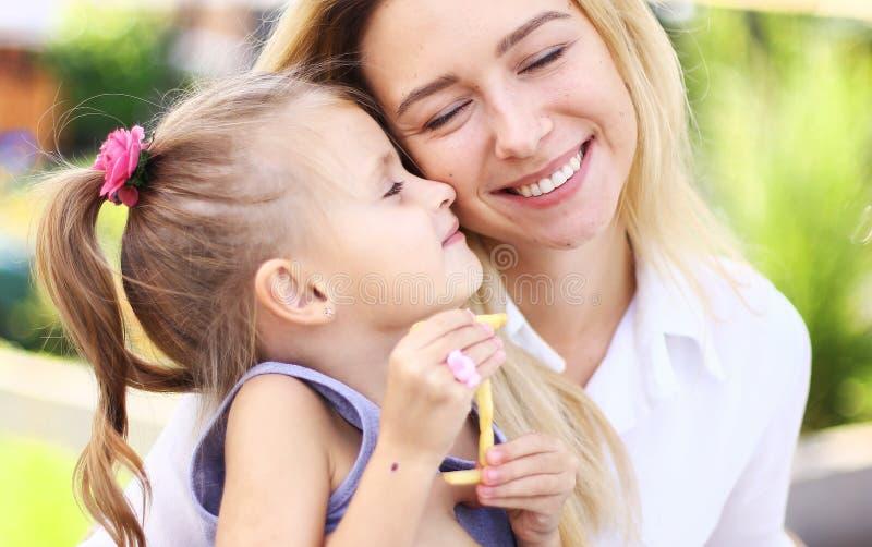 Pequeña hija que abraza a la madre afuera fotos de archivo