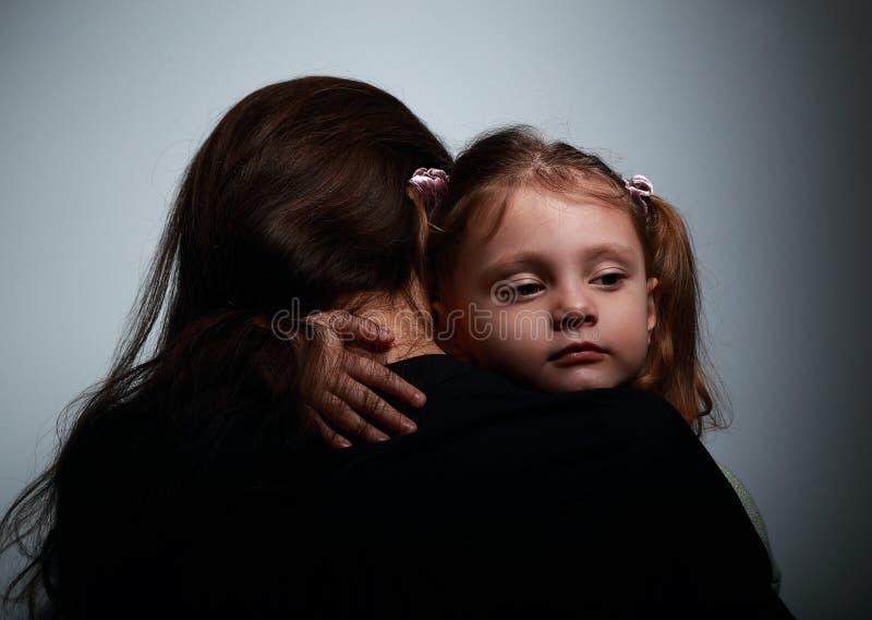 Pequeña hija triste que abraza a su madre con amor en oscuridad fotografía de archivo libre de regalías