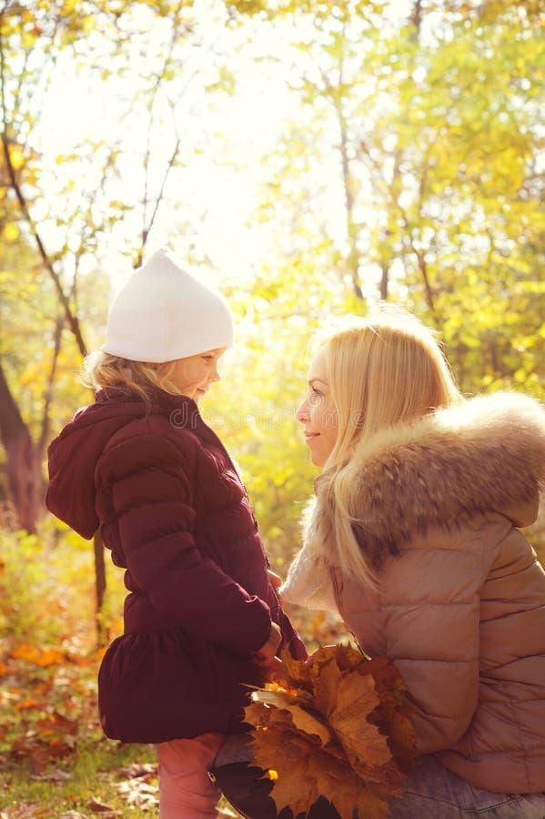 Pequeña hija y su madre que miran uno a y que sonríen, niñez feliz, contraluz en parque del otoño foto de archivo