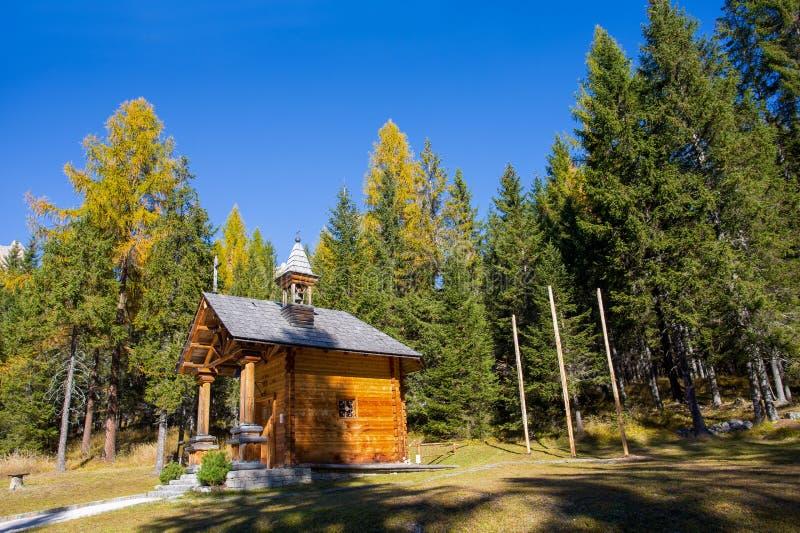 Pequeña iglesia de madera en un paisaje en dolomías, Italia del otoño Montañas, abetos y sobre todo alerces que cambian assumin d fotografía de archivo libre de regalías