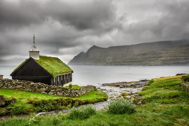 Pequeña iglesia del pueblo debajo de las nubes pesadas fotografía de archivo