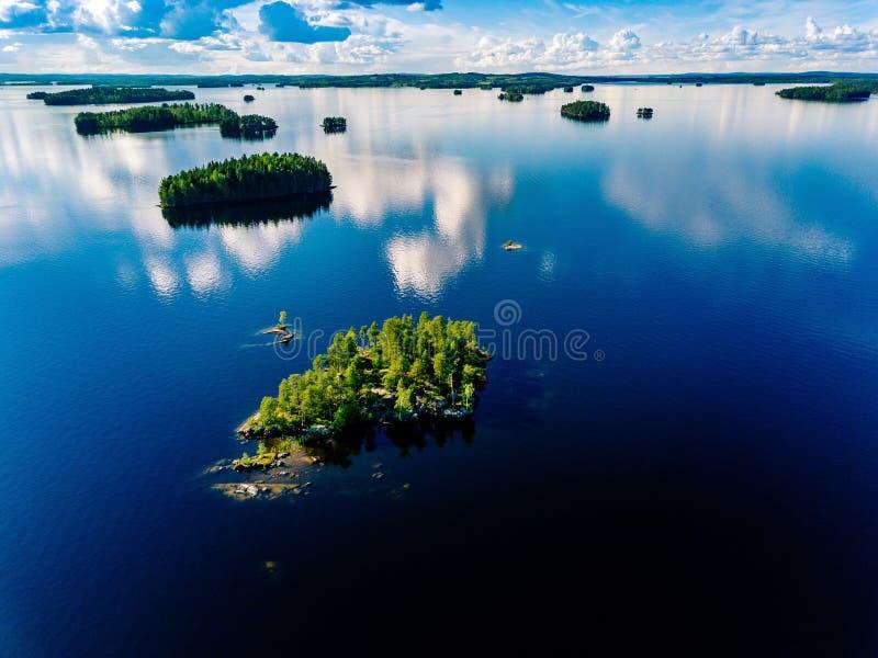 Pequeña isla de la visión aérea en paisaje azul del lago con los bosques verdes en un día de verano soleado en Finlandia fotos de archivo libres de regalías