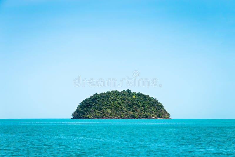 Pequeña isla verde redonda contra el cielo azul foto de archivo libre de regalías