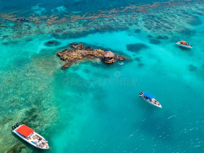 Small island and boats in the caribbean sea royalty free stock photo