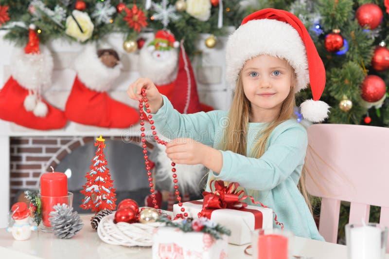 Pequeña jovencita con regalos de Año Nuevo con sombrero de Santa imágenes de archivo libres de regalías