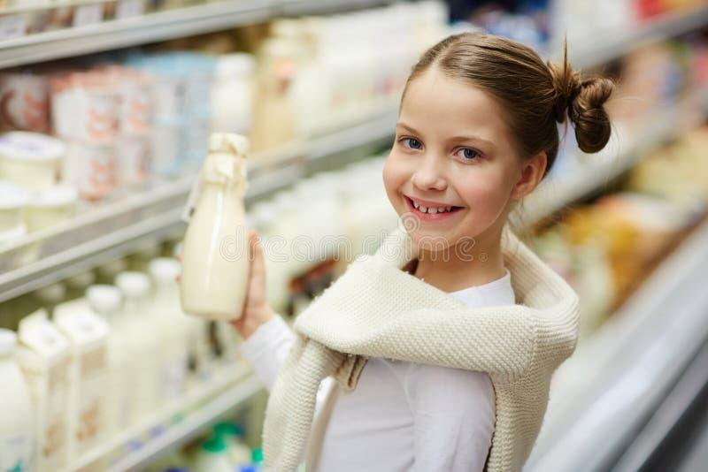 Pequeña leche de compra sonriente de la muchacha imagenes de archivo