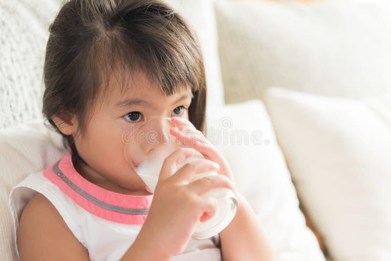 Pequeña mano asiática feliz de la muchacha que sostiene la leche de consumo de cristal foto de archivo libre de regalías
