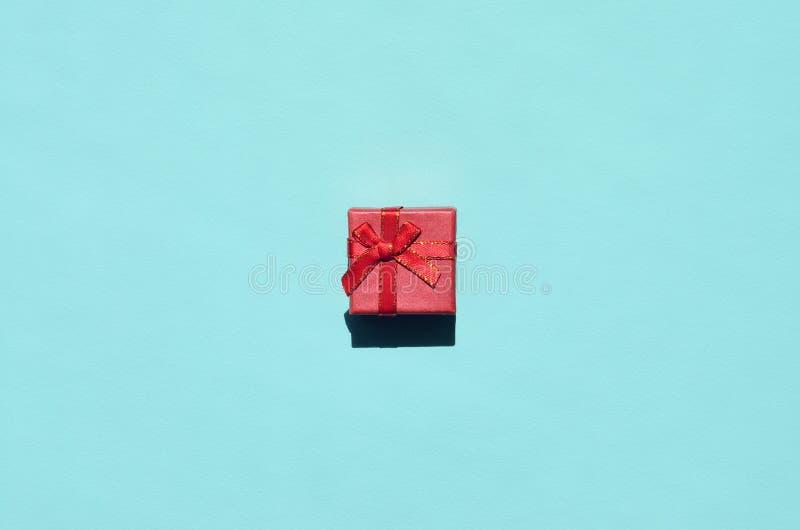Pequeña mentira rosada roja de la caja de regalo en el fondo de la textura del papel azul en colores pastel de moda del color de  fotografía de archivo