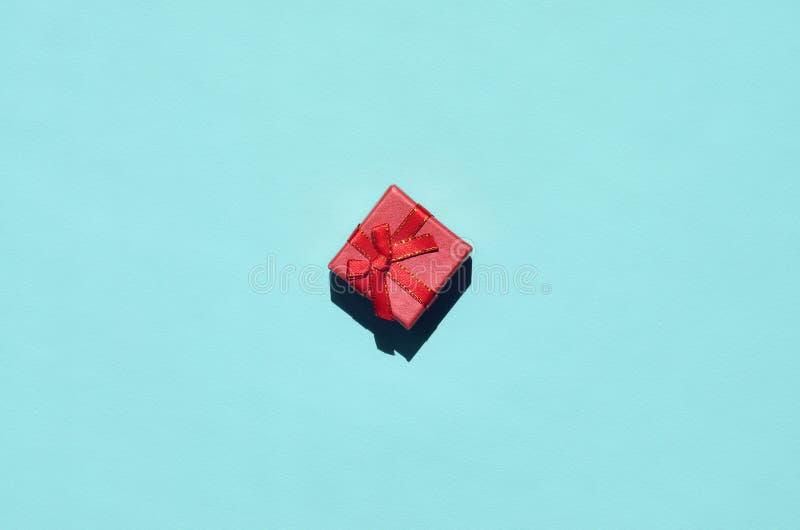 Pequeña mentira rosada roja de la caja de regalo en el fondo de la textura del papel azul en colores pastel de moda del color de  imagen de archivo