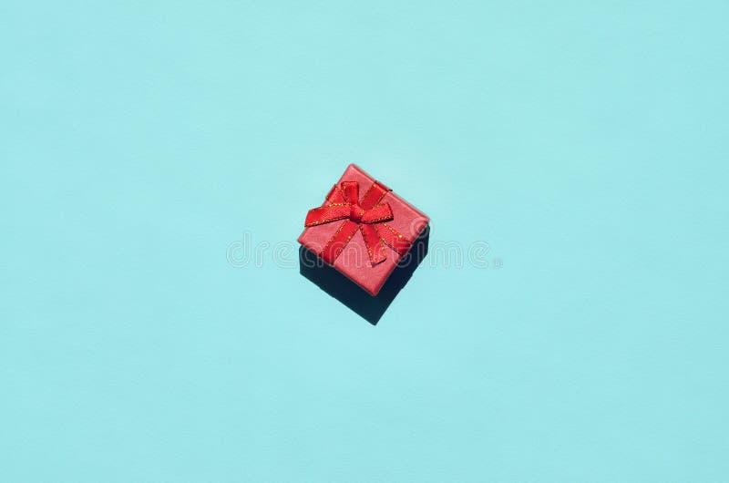 Pequeña mentira rosada roja de la caja de regalo en el fondo de la textura del papel azul en colores pastel de moda del color de  foto de archivo