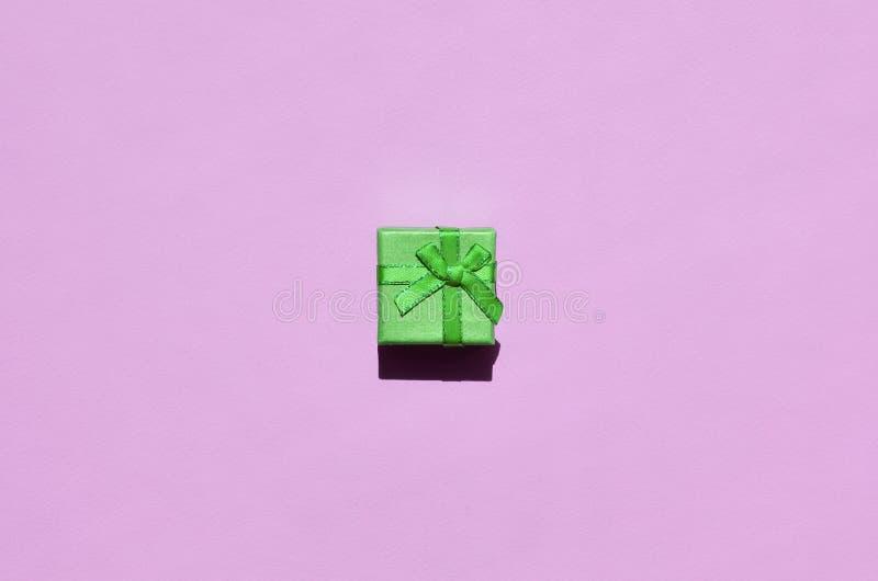 Pequeña mentira verde de la caja de regalo en el fondo de la textura del papel rosado en colores pastel de moda del color de la m fotos de archivo