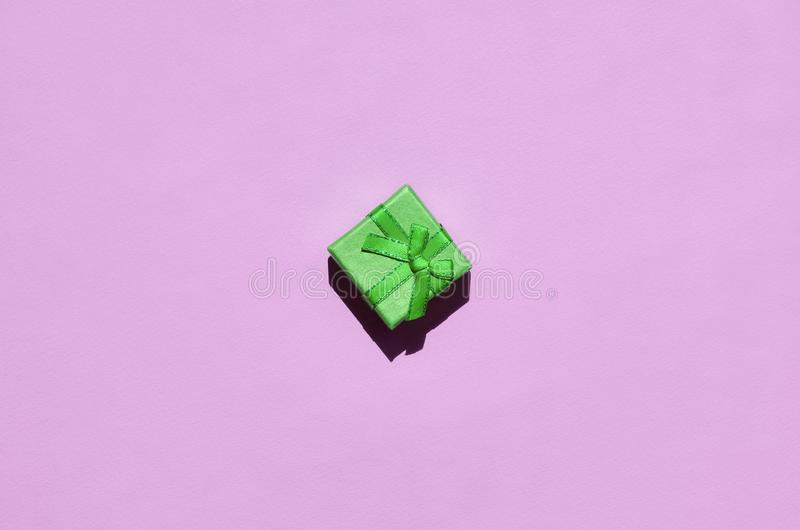 Pequeña mentira verde de la caja de regalo en el fondo de la textura del papel rosado en colores pastel de moda del color de la m imagen de archivo libre de regalías