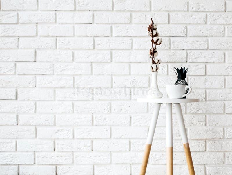 Pequeña mesa de centro con la taza y la decoración en los vagos blancos de la pared de ladrillo fotografía de archivo libre de regalías