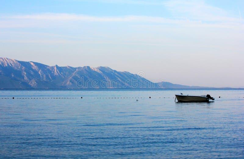 Pequeña motora en el mar en la salida del sol fotos de archivo