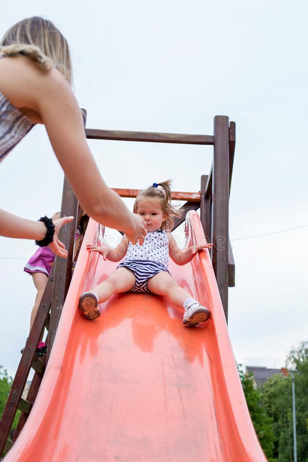 Pequeña muchacha adorable en diapositiva en el patio de los niños fotos de archivo