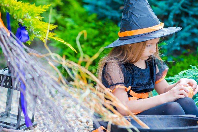 Pequeña muchacha adorable en el traje de Halloween con grande imagen de archivo