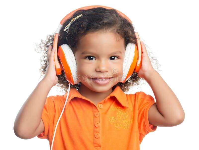 Pequeña muchacha afroamericana con los auriculares anaranjados brillantes fotos de archivo libres de regalías