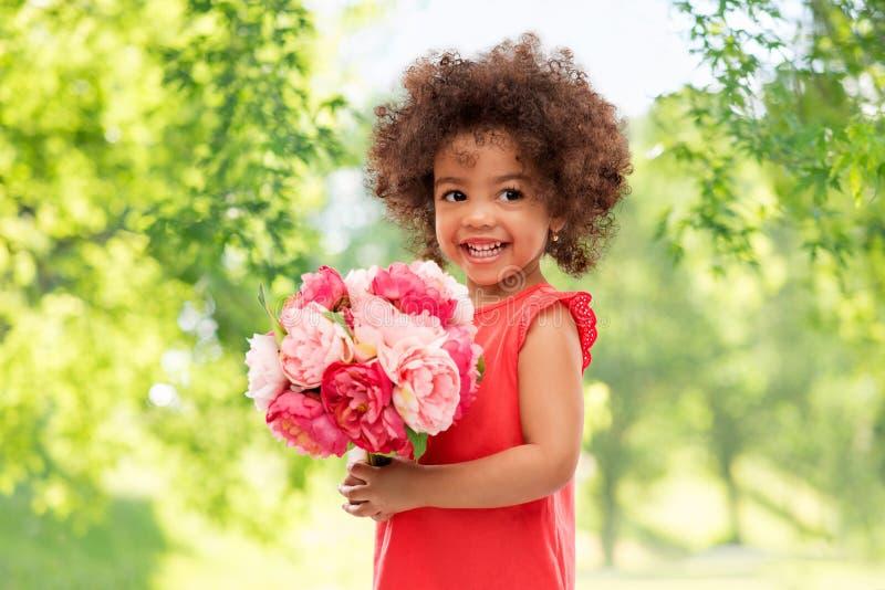 Pequeña muchacha afroamericana feliz con las flores fotos de archivo