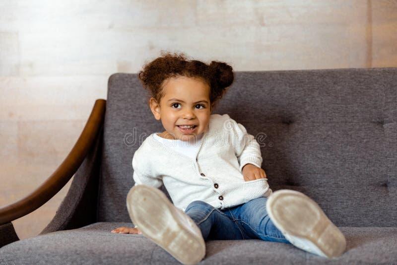 Pequeña muchacha afroamericana que se sienta en el sofá en casa fotografía de archivo