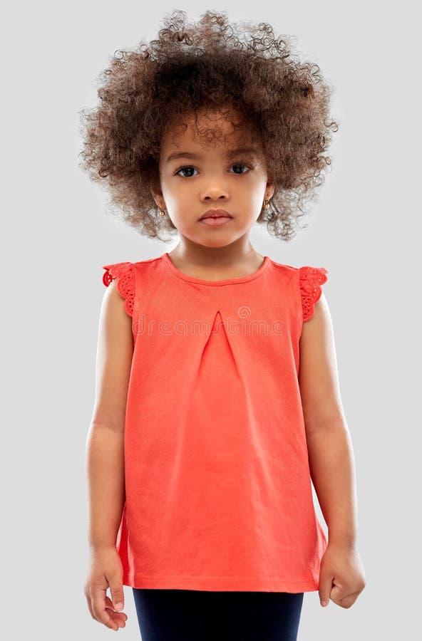 Pequeña muchacha afroamericana triste sobre gris foto de archivo libre de regalías