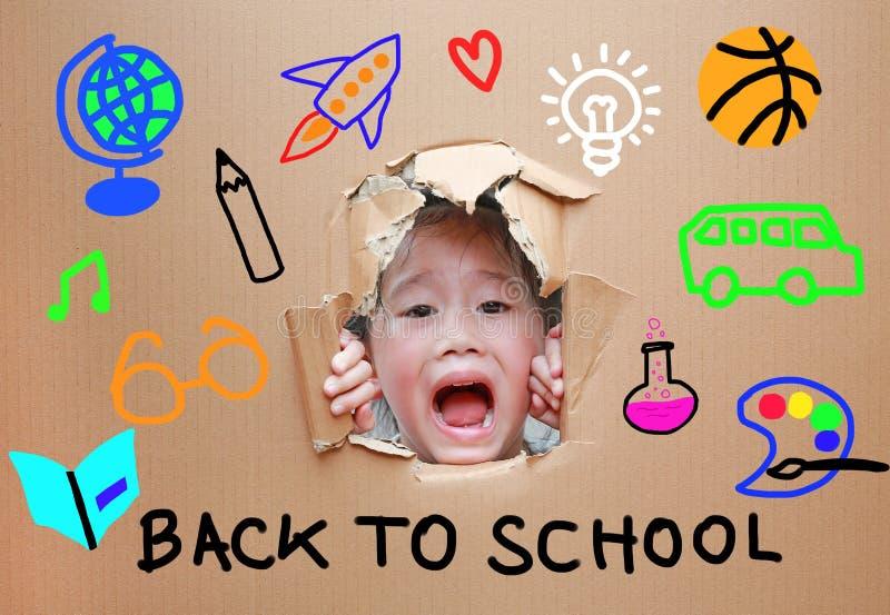 Pequeña muchacha asiática adorable del niño que mira a través del agujero en la cartulina con de nuevo a la escuela y el concepto foto de archivo