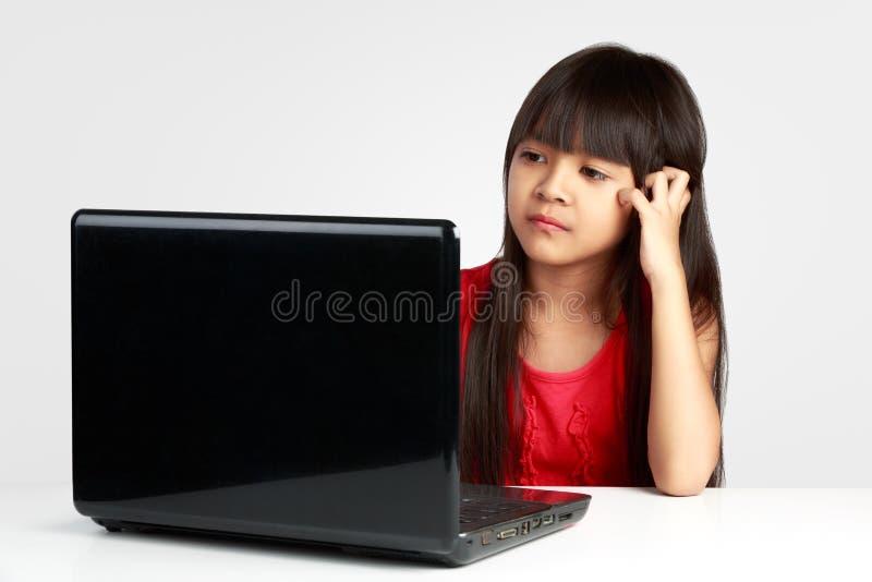Pequeña muchacha asiática agotadora que trabaja en el ordenador portátil foto de archivo libre de regalías
