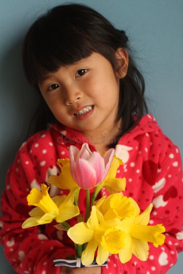 Pequeña muchacha asiática con las flores fotografía de archivo
