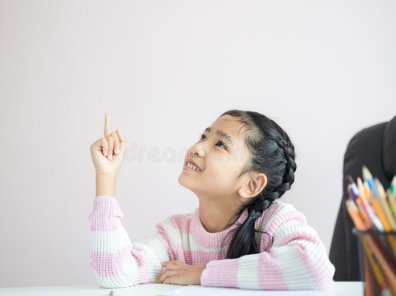 Pequeña muchacha asiática del retrato que señala el finger y la sonrisa con felicidad con la profundidad baja del foco selecto de fotografía de archivo