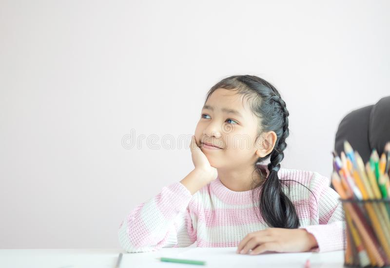 Pequeña muchacha asiática del retrato que se sienta en la barbilla y la sonrisa con la metáfora de la felicidad que piensa algo c imagen de archivo libre de regalías