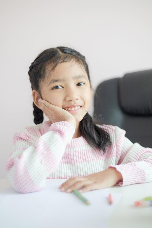 Pequeña muchacha asiática del retrato que se sienta en la barbilla y la sonrisa con la metáfora de la felicidad que piensa algo c fotografía de archivo