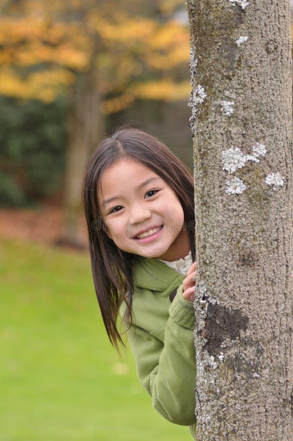 Pequeña muchacha asiática detrás de un árbol foto de archivo