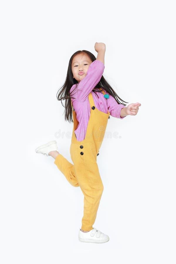 Pequeña muchacha asiática divertida del niño en los overoles rosado-amarillos que saltan sobre el fondo blanco Concepto del movim foto de archivo