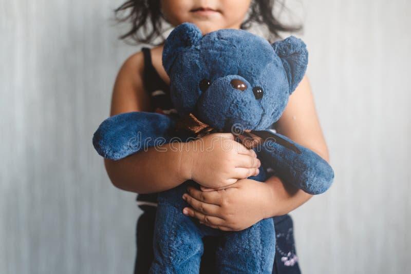 Pequeña muchacha asiática dulce que abraza su oso de peluche preferido del juguete fotografía de archivo