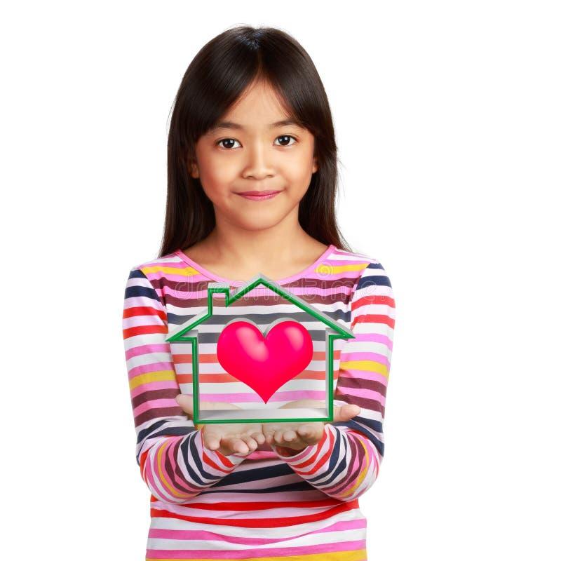 Pequeña muchacha asiática feliz con la casa virtual foto de archivo libre de regalías