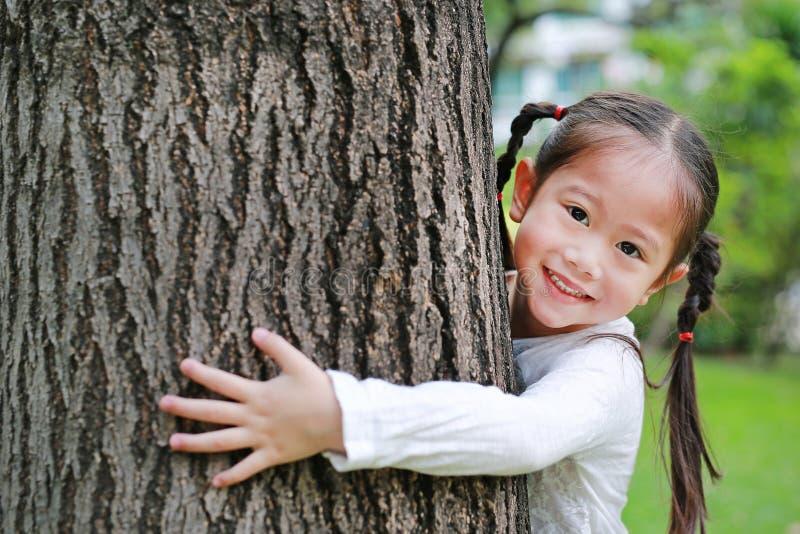 Pequeña muchacha asiática feliz del niño que abraza un árbol grande en el jardín imagen de archivo