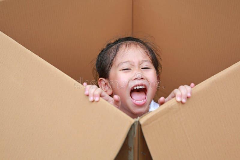 Pequeña muchacha asiática feliz del niño que juega peekaboo y mentira en caja de cartón grande imágenes de archivo libres de regalías